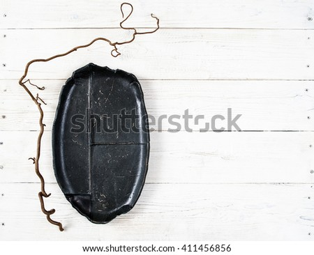 Top view empty black oval plate on rustic wooden table. Ceramic creative black plate on white wooden background with free space. Flat lay of handmade black dish on white wooden table.  - stock photo