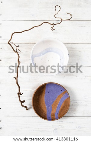 Top view empty creative handmade pottery plates with turquoise pattern on rustic wooden table.  Flat lay set of colorful clay dishes on white wooden background.  - stock photo