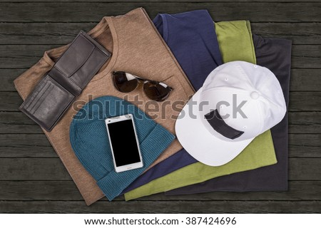 Top view flat lay hipster clothes and accessories on a wooden background. Travel and vacation template concept - stock photo