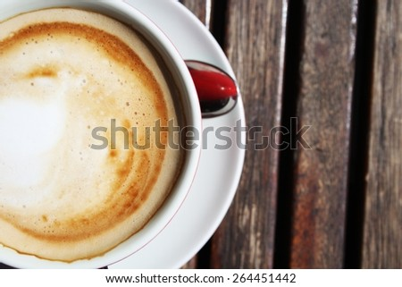 Top view, from above, cup of espresso coffee with milk on wooden background - stock photo