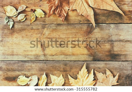 top view image of autumn leaves over wooden textured background  - stock photo