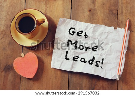 top view image of coffee cup, heart shape and paper with the phrase get more leads over wooden background - stock photo
