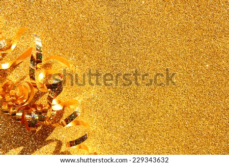 top view image of curly golden ribbon over textured glitter background - stock photo
