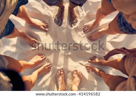 Top view image of feet of young people standing in a circle. Mixed race friends standing barefoot on sandy beach. Concept of unity in diversity. - stock photo