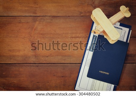 top view image of flying ticket wooden airplane and passport over wooden table - stock photo