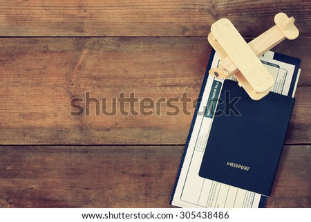 top view image of flying ticket wooden airplane and passport over wooden table. retro filtered image - stock photo