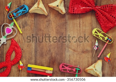 top view image of Hamantaschen cookies or hamans ears,noisemaker and mask for Purim celebration (jewish carnival holiday)  - stock photo