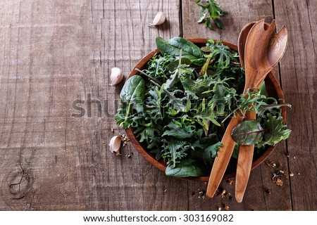 Top view image of leafy green mix of kale, spinach, baby beetroot leaves and garlic over rustic wooden background with copyspace - stock photo