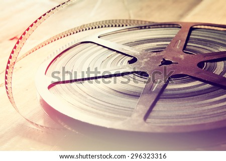 top view image of old 8 mm movie reel over wooden background  - stock photo
