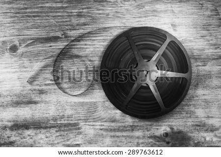 top view image of old 8 mm movie reel over wooden background. black and white photo - stock photo
