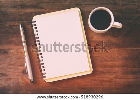 top view image of open notebook with blank pages next to cup of coffee on wooden table. ready for adding text or mockup. Retro filtered and toned