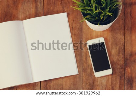 top view image of open notebook with blank pages next to smartphone  on wooden table. ready for adding text or mockup - stock photo