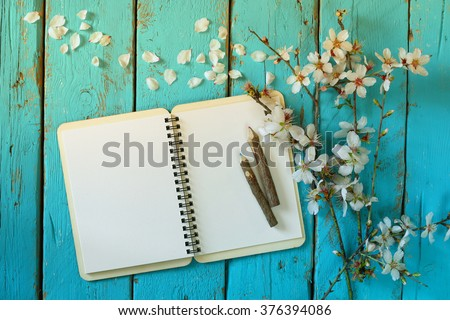top view image of spring white cherry blossoms tree, open blank notebook  next to wooden colorful pencils on blue wooden table. vintage filtered and toned image - stock photo