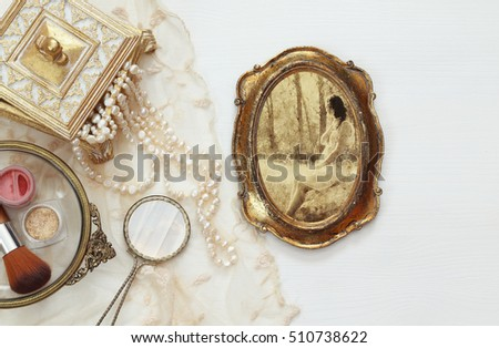 Top view image of vintage woman toilet fashion objects next to photo frame with photography of beautiful woman on wooden table
