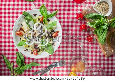 Top view italian vegetable salad with cabbage, kidney bean, cherry tomatoes dressed with balsamic vinegar and olive oil on the  white plate on kitchen tablecloth with different bright ingredients - stock photo