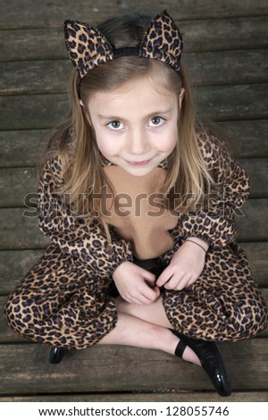 top view little girl disguised as a leopard seated on a wooden floor - stock photo