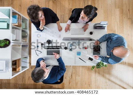Top view, Meeting for the business team, brainstorming for the new project, they sit around a white desk. Focus on the table - stock photo