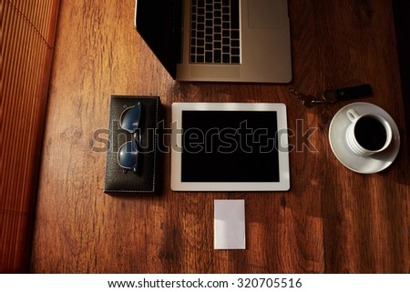 Top view mock up of businessman luxury accessories and work tools, cup of american coffee, sunglasses, envelope, digital tablet and laptop computer, office workplace desktop, hipster freelance loft - stock photo