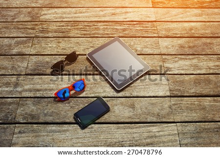 Top view mock up presentation with blank screen digital tablet, smart phone and couple of sunglasses lying on the wooden texture, vacation holidays or recreation time concept, flare sun light - stock photo