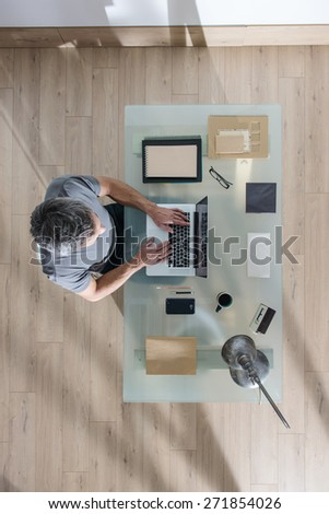 top view, Modern businessman sitting at glass desk and working on his laptop, his table is perfectly tidy, the sun casts graphics shadows on the wood floor - stock photo