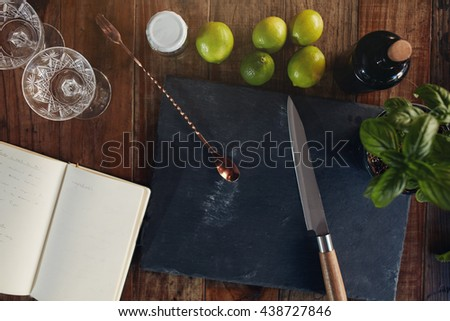 Top view of a bar counter with chopping board, knife, spoon, lime, basil leaves, glasses and a diary. Preparing a perfect cocktail. - stock photo