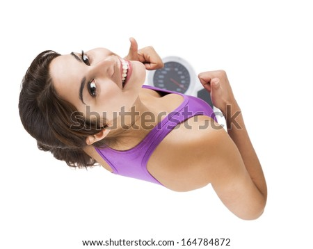 Top view of a beautiful athletic woman over a scale with thumbs up, isolated on white - stock photo