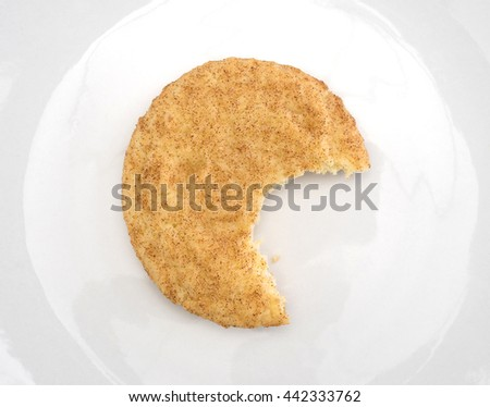 Top view of a bitten snickerdoodle cookie on an off white plate.
