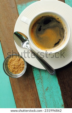Top view of a black coffee in white cup with sugar on old wood background. - stock photo