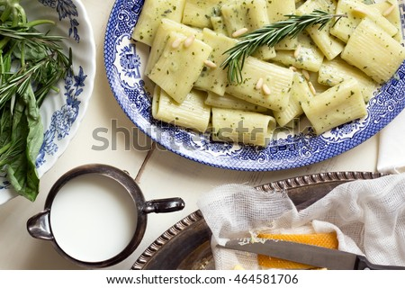 Top view of a blue china platter filled with pesto rigatoni. Fresh herbs, creamer, and cheese also on table. Rosemary garnish.