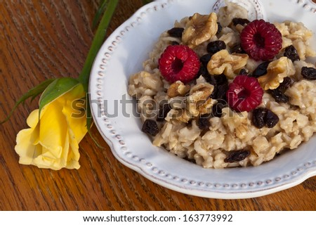 Top view of a bowl of oatmeal with walnuts, raisins, and red raspberries next to a yellow rose on a weathered wooden chair - stock photo