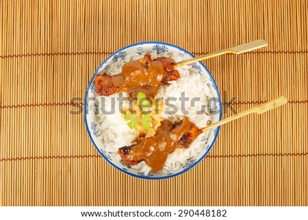 Top view of a bowl of rice with two grilled pork skewers and satay sauce - stock photo