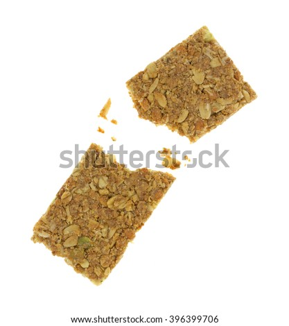 Top view of a broken cinnamon flavored sesame and pumpkin seed granola bar isolated on a white background.