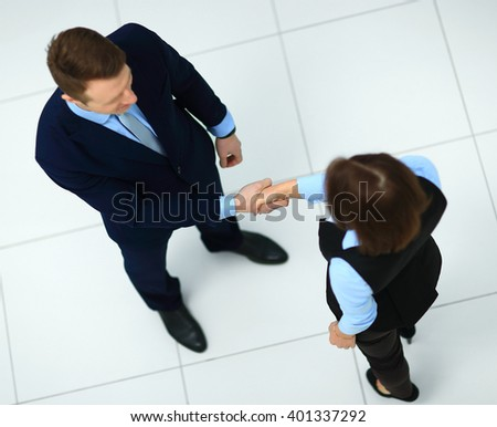 Top view of a businessman and businesswoman shaking hands - Welcome to business