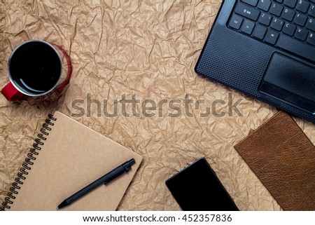 top view of a computer, laptop, cake, cup of coffee, notebook, smart phone, and office work space vintage style