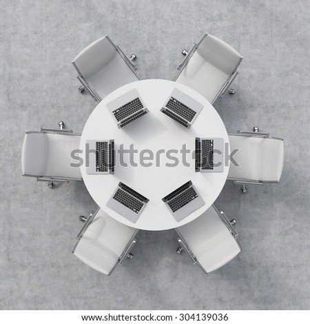 Top view of a conference room. A white round table, six chairs. Six laptops are on the table. Office interior. 3D rendering. - stock photo
