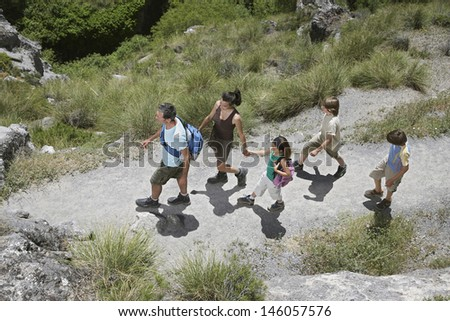 Top view of a couple with three children walking along mountain path - stock photo