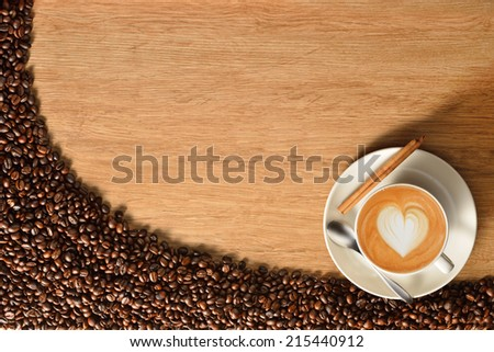 Top view of a cup of coffee and coffee beans on old wooden background - stock photo