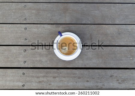 Top view of a cup of coffee on vintage wooden floor - stock photo