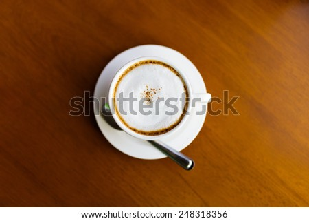 Top view of a cup of coffee with teaspoon on wooden table - stock photo
