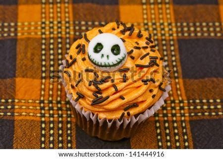 Top view of a cupcake with a skull design displayed on a table cloth. - stock photo