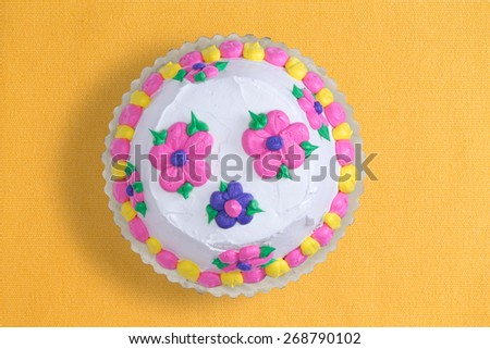 Top view of a decorative iced homemade cake with colorful pink and blue flowers surrounded with a yellow and pink alternating border, served uncut on a yellow background with copy space