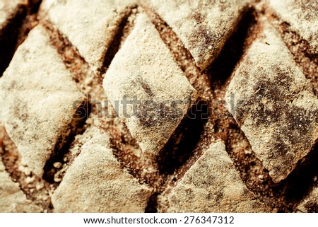 Top view of a decorative loaf of freshly baked gourmet bread with a diamond pattern incised in the crust - stock photo