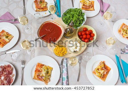 Top view of a dinner table with pizza slices on the plates and pizza ingredients in the middle: tomato sauce, arugula, cherry tomato, mozzarella balls and corn; prosciutto on the side - stock photo