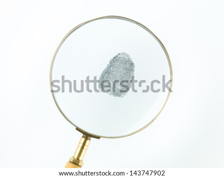 top view of a fingerprint viewed through a magnifying glass, against a white background - stock photo