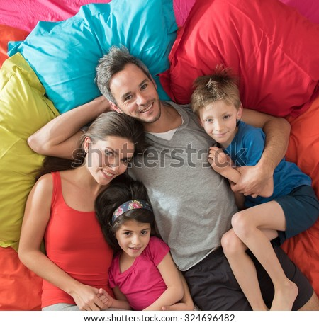 top view of a four people family laying on their sofa with large cushions. They are cuddling, the grey hair father is hugging his wife and his blond son and the mother is holding her daughter - stock photo