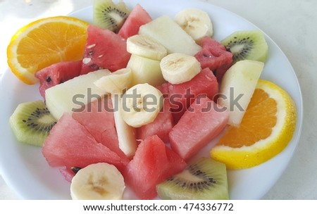 Top view of a fruit salad with watermelon, oranges, kiwi, melon and bananas
