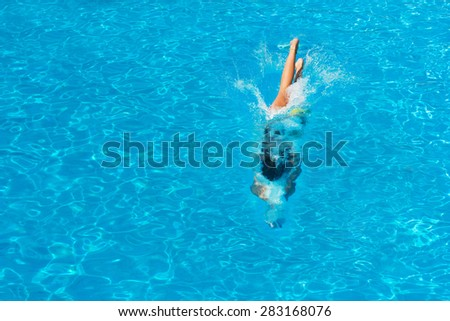 Top view of a  girl diving in the swimming pool - stock photo