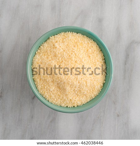 Top view of a green bowl filled with freshly grated parmesan cheese on a marble cutting board.