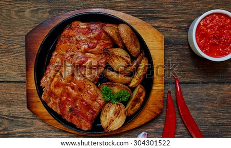 Top view of a housewife in the oven baked pork ribs with onion, meat cooked in tomato sauce and garlic spices - stock photo