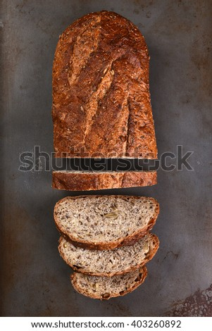 Top view of a loaf of multi-grain bread on a baking sheet. The loaf is partially sliced,  - stock photo